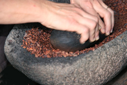 Grinding cocoa nibs on a stone metate.