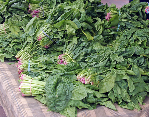Bunches of spinach for sale at a farmers market.