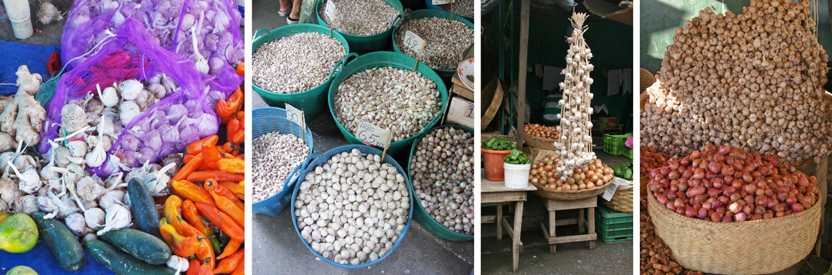 Garlic offered for sale in markets throughout the world (L-R): amid other vegetables in Peru, tubs of bulbs and separated cloves in Thailand, hanging braids in Nicaragua, and huge pile in Madagascar (behind basket of onions).