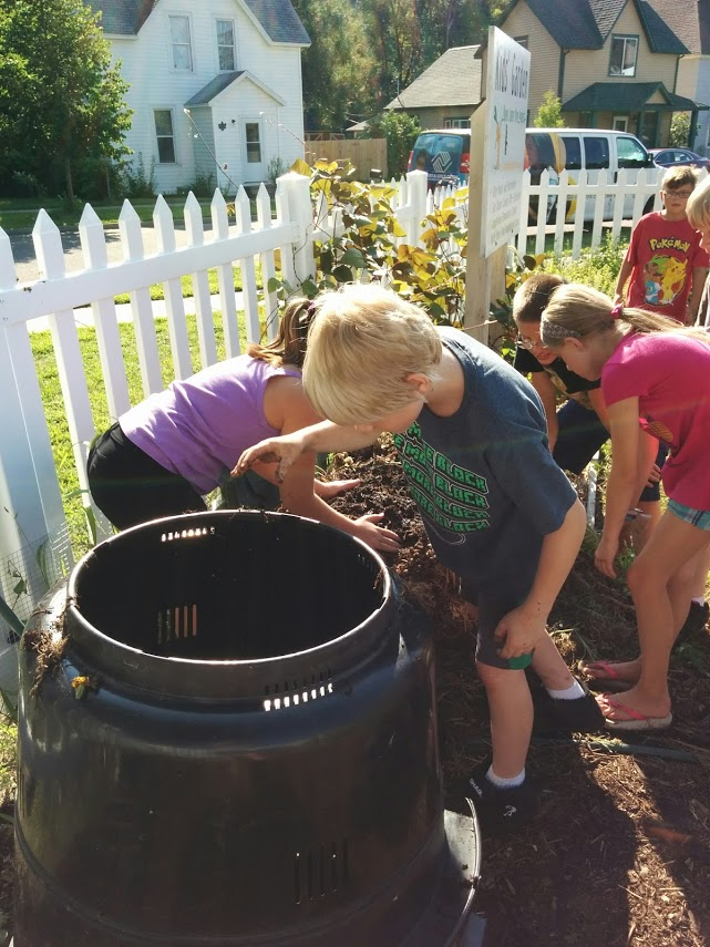 Eau Claire County Master Gardener Volunteers get kids churning compost.