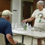 A Master Gardener Volunteer shows monarch butterfly larva specimens to memory impaired participants of SPARK! i