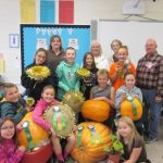 students posing with pumpkins