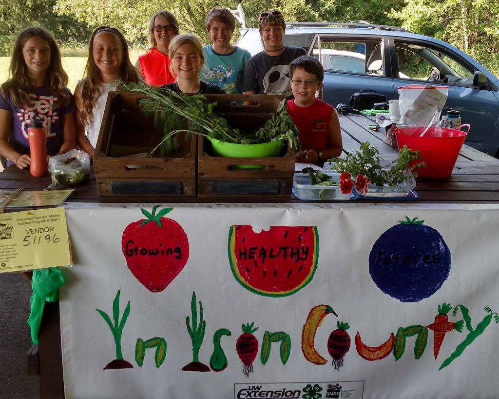 Children posing with vegetables they harvested