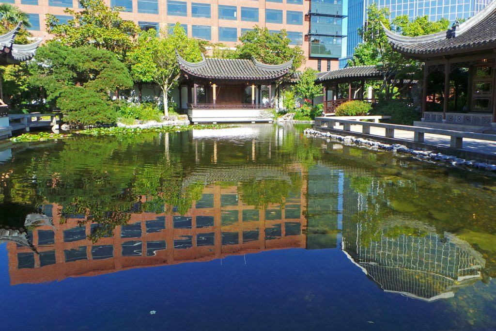 the lan su chinese garden is surrounded by the tall buildings of downtown portland reflected in lake zither - Chinese Garden Portland
