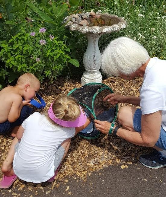 Woman teaching kids about butterflies